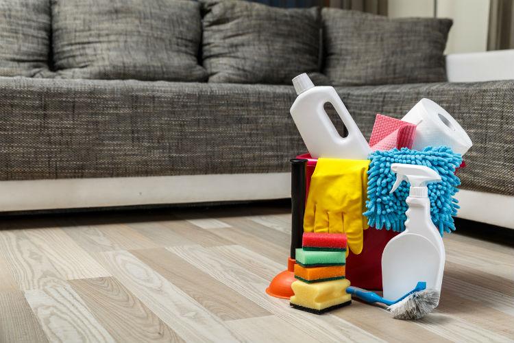 Putzmittel und Ausrüstung stehen vor einen Couch