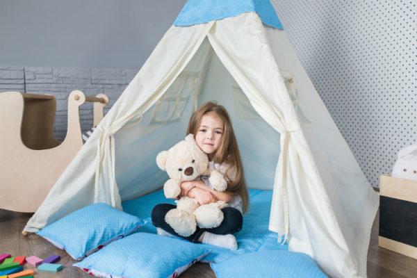 Wohlfühl-Kinderzimmer - Mädchen sitzt in Spielezelt im Kinderzimmer