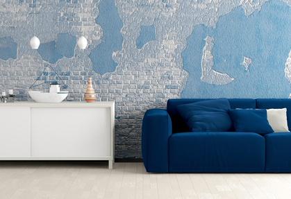 Eine helle Kommode und ein blaues Sofa in einem maritimen Wohnzimmer.
