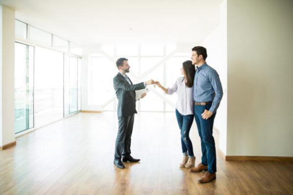 Immobilienmakler übergibt seinen Kunden den Schlüssel in der neue Immobilie