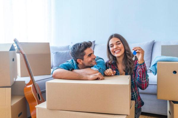 Ein Paar welches Kartons packt und lacht