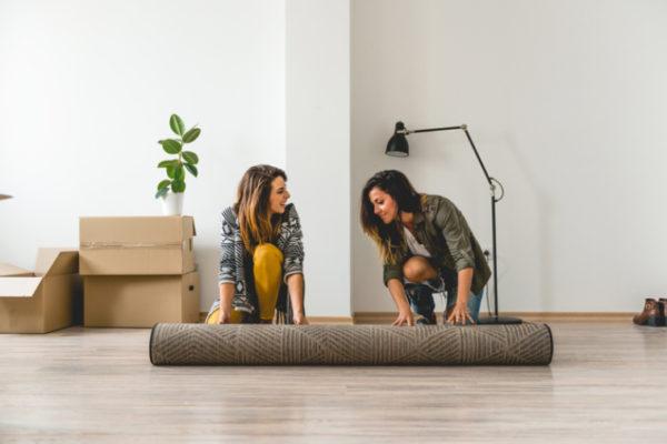 Zwei Frauen rollen einen Teppich aus