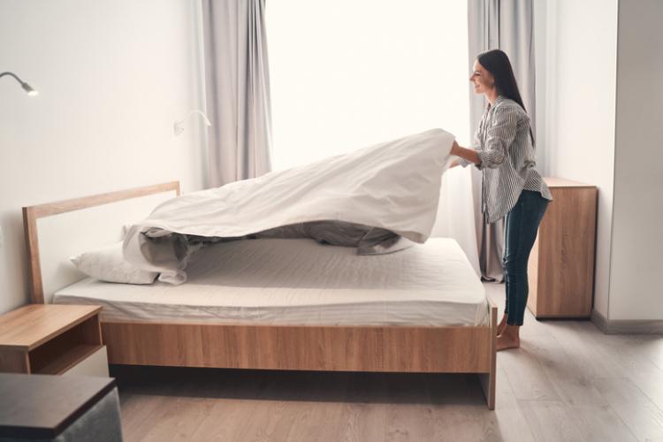 Frau wechselt Bettwäsche