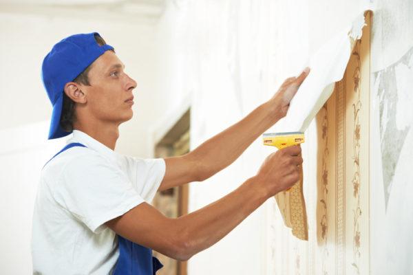 Maler entfernt Tapete von der Wand