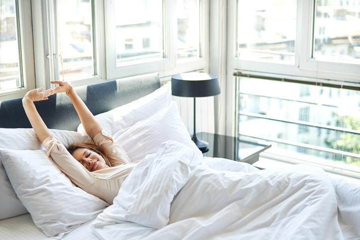 Frau wacht glücklich in Bett auf