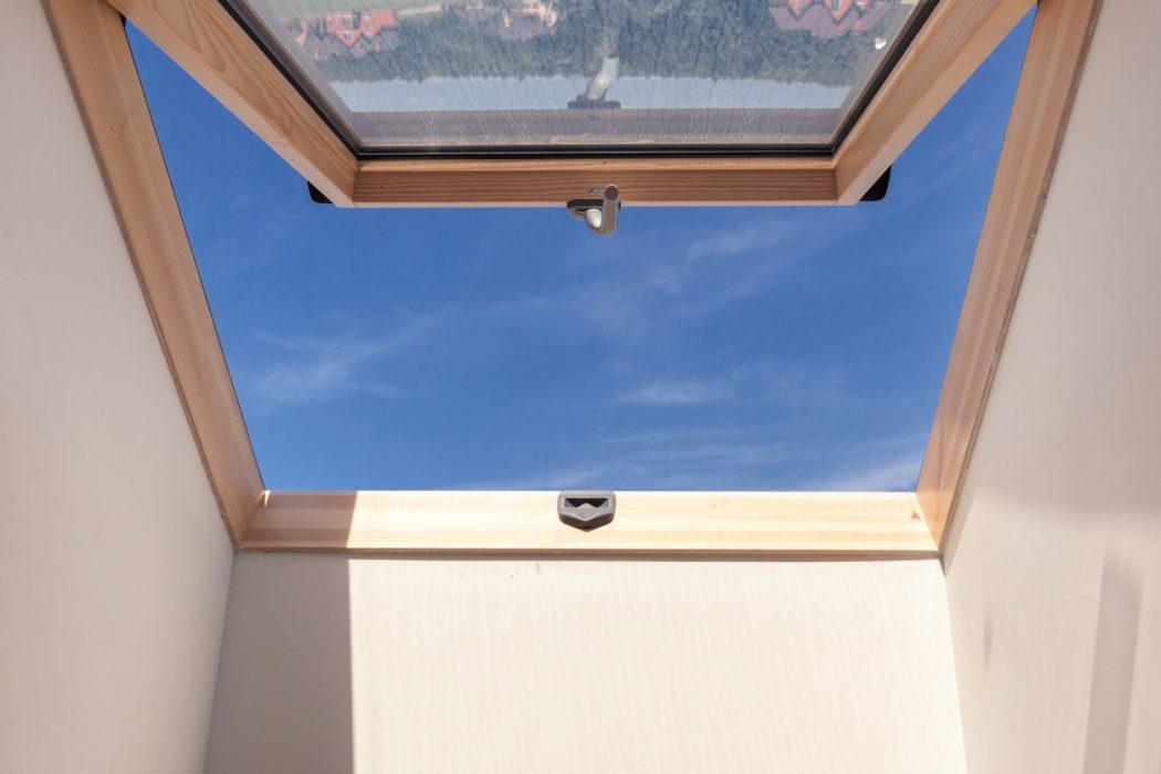 Blick in den Himmel durch halb geöffnetes Dachfenster