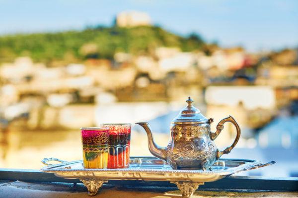 Nahaufnahme eines orientalischen Teeservice mit Marokko im Hintergrund