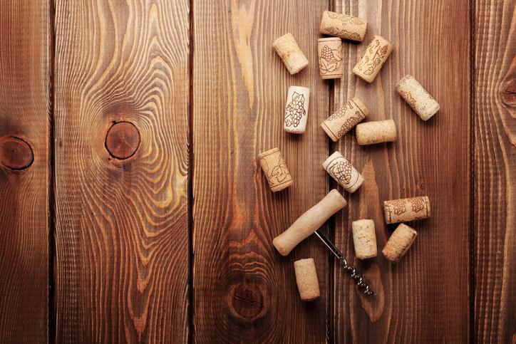 Korken und ein Korkenzieher auf einem Holzhintergrund