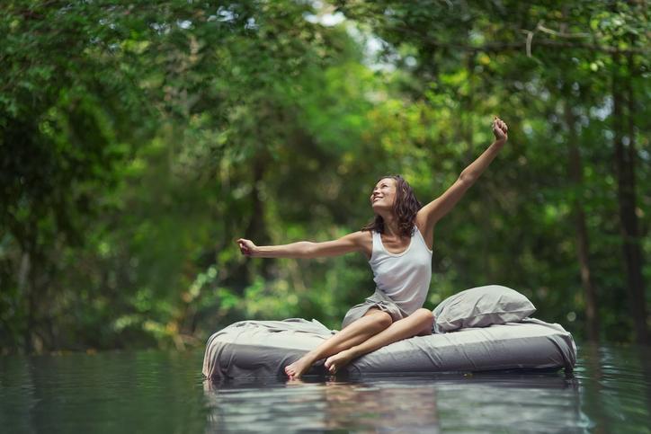Frau erwacht auf Bett im Wasser