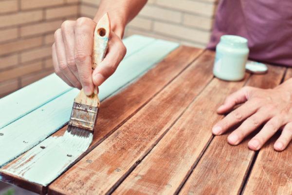 Person die Tisch lackiert