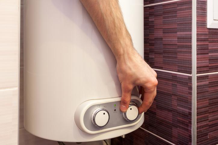 Mann reguliert Temperatur am Boiler einer Heizung