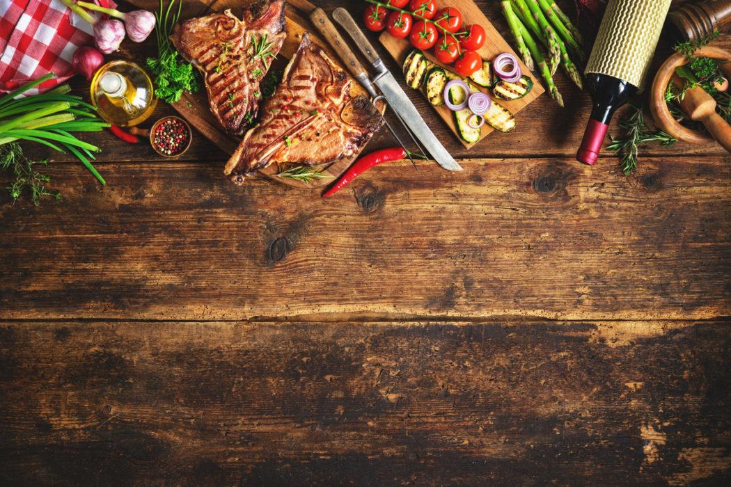 Grillfleisch und Beilagen auf einem Holzuntergrund