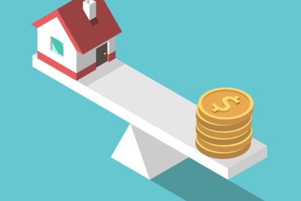 Haus auf einem Balanceakt mit Münzen