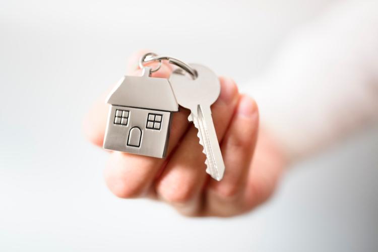 Hand mit Schlüsselbund mit Schlüssel und Hausanhänger