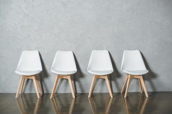 4 weiße Stühle sind nebeneinander aufgereiht