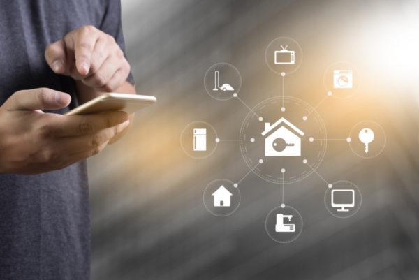 Mann steuert von seinem Handy sein Smart Home