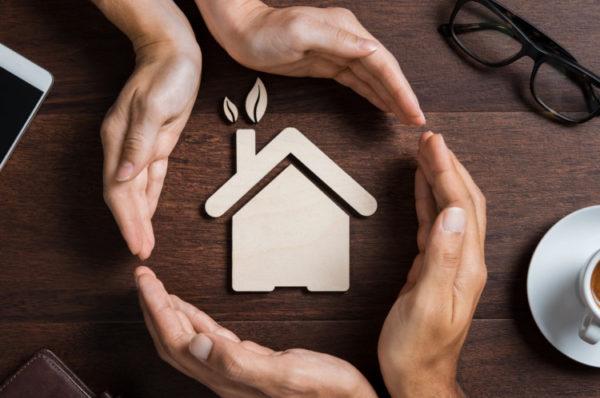 Hand die ein Haus aus Holz umschließt