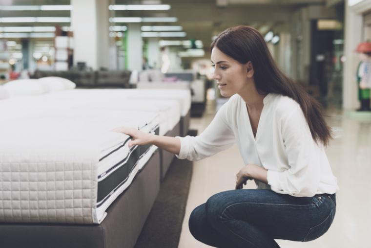 Frau die sich eine Matratze anschaut