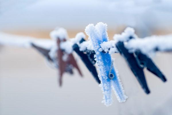 eingefrorene Wäscheklammer hängt an einer Wäscheleine