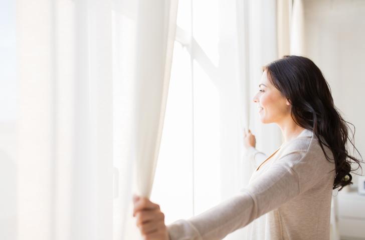 Frau öffnet Vorhänge