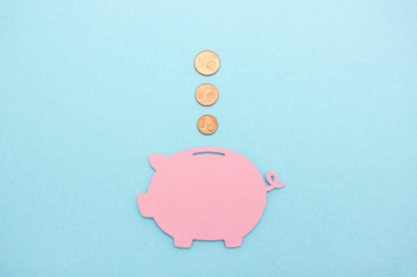 Sparschwein welches mit Münzen gefüllt wird