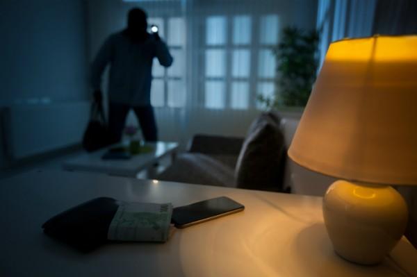 Einbrecher mit Taschenlampe in wenig beleuchteten Raum