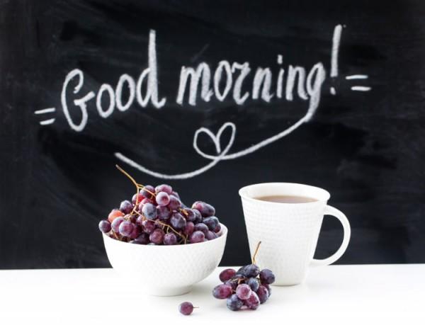 Schriftzug auf einer Tafelwand mit einer Tasse Kaffee und einer Schale Früchte.
