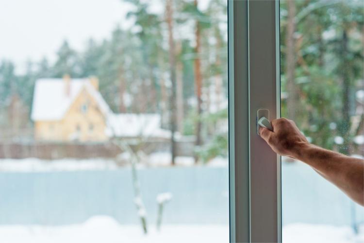 Eine männliche Hand öffnet ein Fenster. Im Hintergrund ist eine winterliche Landschaft zu sehen.